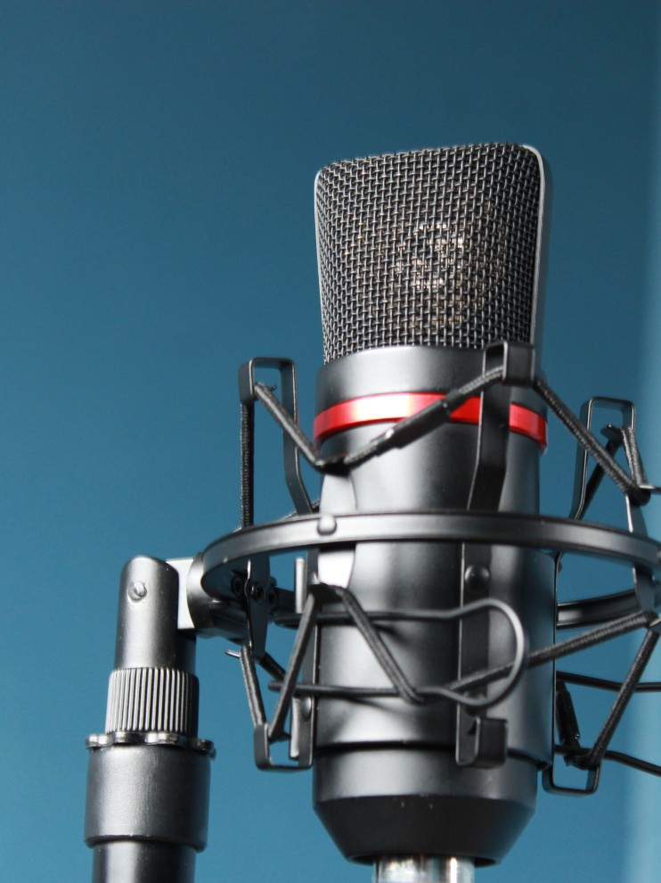 close up shot of a broadcasting microphone on a plain blue background